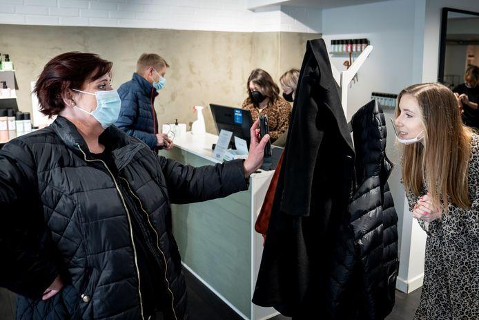 Een klant toont via de app haar negatieve coronatest aan de kapster.