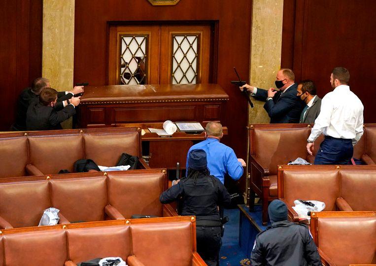 Veiligheidsmensen houden betogers onder schot die het Amerikaanse Huis van Afgevaardigden willen binnendringen. Beeld AFP