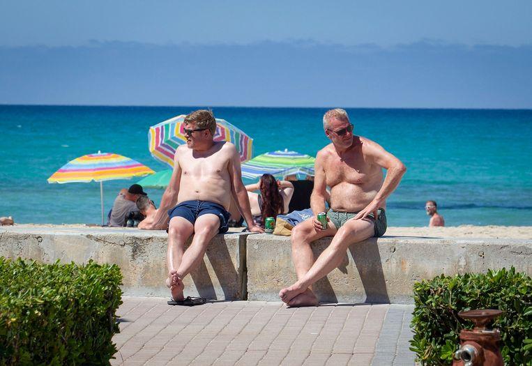 Toeristen drinken een biertje in de zon op Mallorca. Beeld AFP