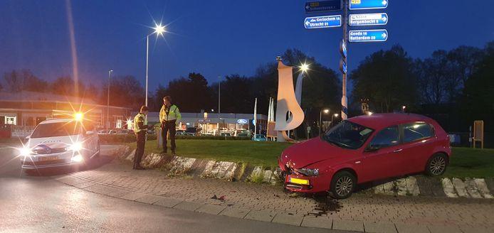De auto bleef hangen op de betonnen rand van de rotonde