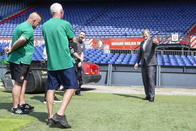 Koning Willem-Alexander praat op het veld van De Kuip met medewerkers van de veldploeg en de technische dienst tijdens een werkbezoek aan het stadion in het kader van de impact van de coronapandemie op de evenementenbranche. Beeld ANP