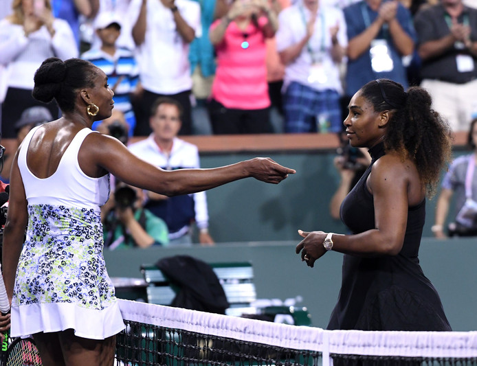 Venus Williams (links) neemt in Indian Wells de felicitaties in ontvangst van zus Serena.