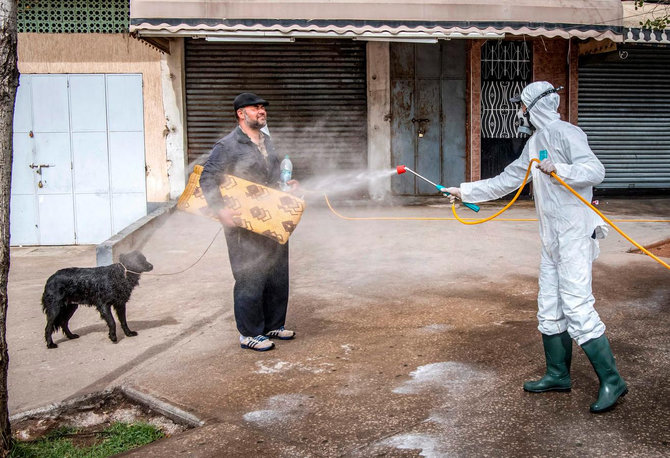 Een  medewerker van het Marokkaanse ministerie van Volksgezondheid sproeit desinfectiemateriaal over een man en zijn hond, in de hoofdstad Rabat.