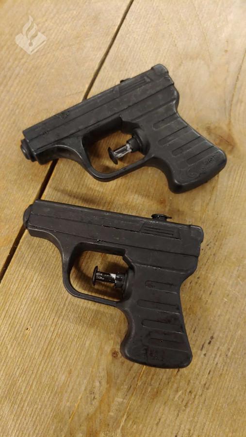 De zwart geverfde waterpistooltjes