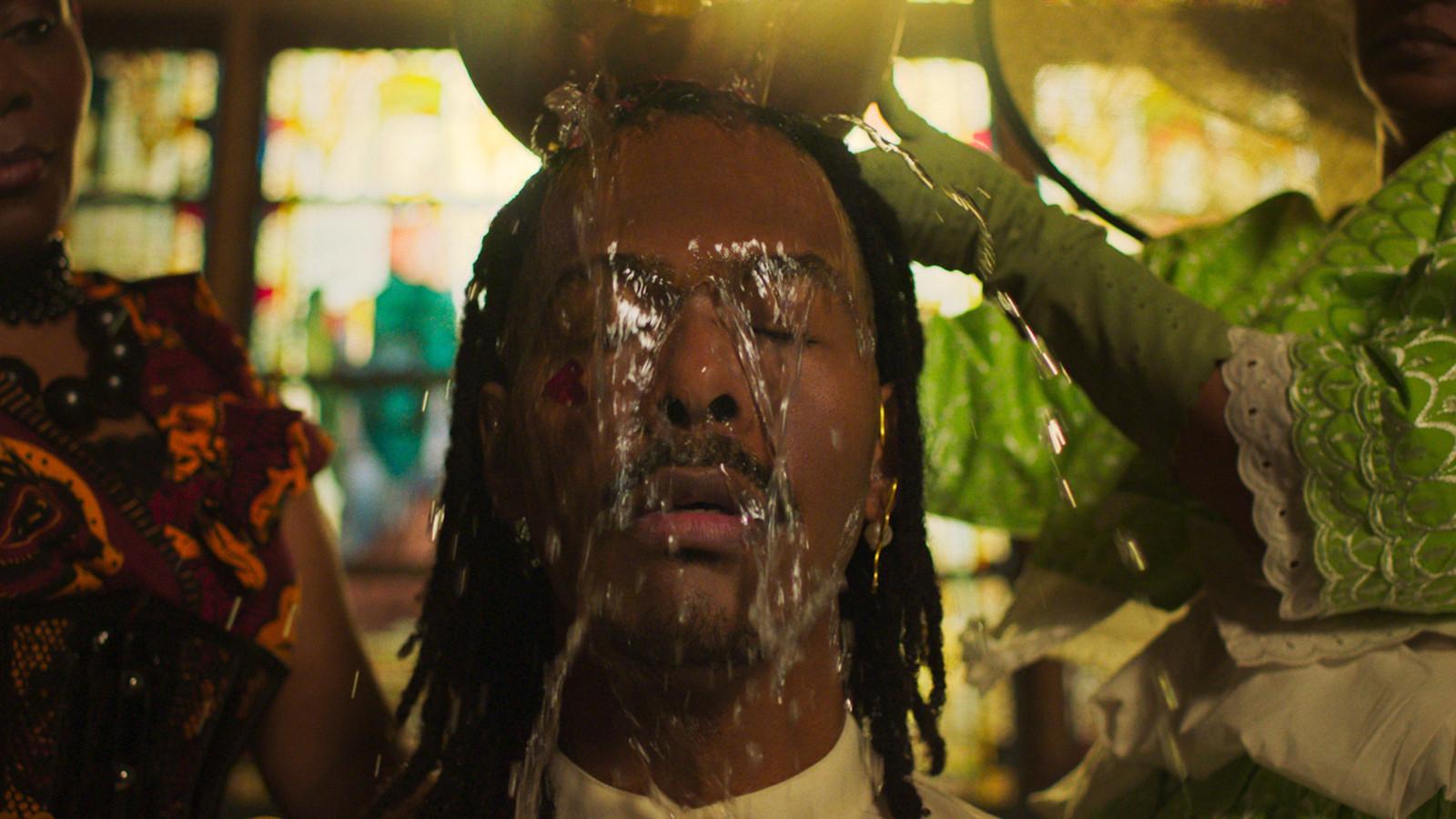 Een andere veelbetekenende still uit de clip van 'Birth Of A New Age' : zanger Jeangu Macrooy ondergaat een 'wasi', een winti-ritueel dat voor spirituele reiniging staat. Koloniale machthebbers verboden winti in de overzeese gebiedsdelen in de negentiende eeuw.