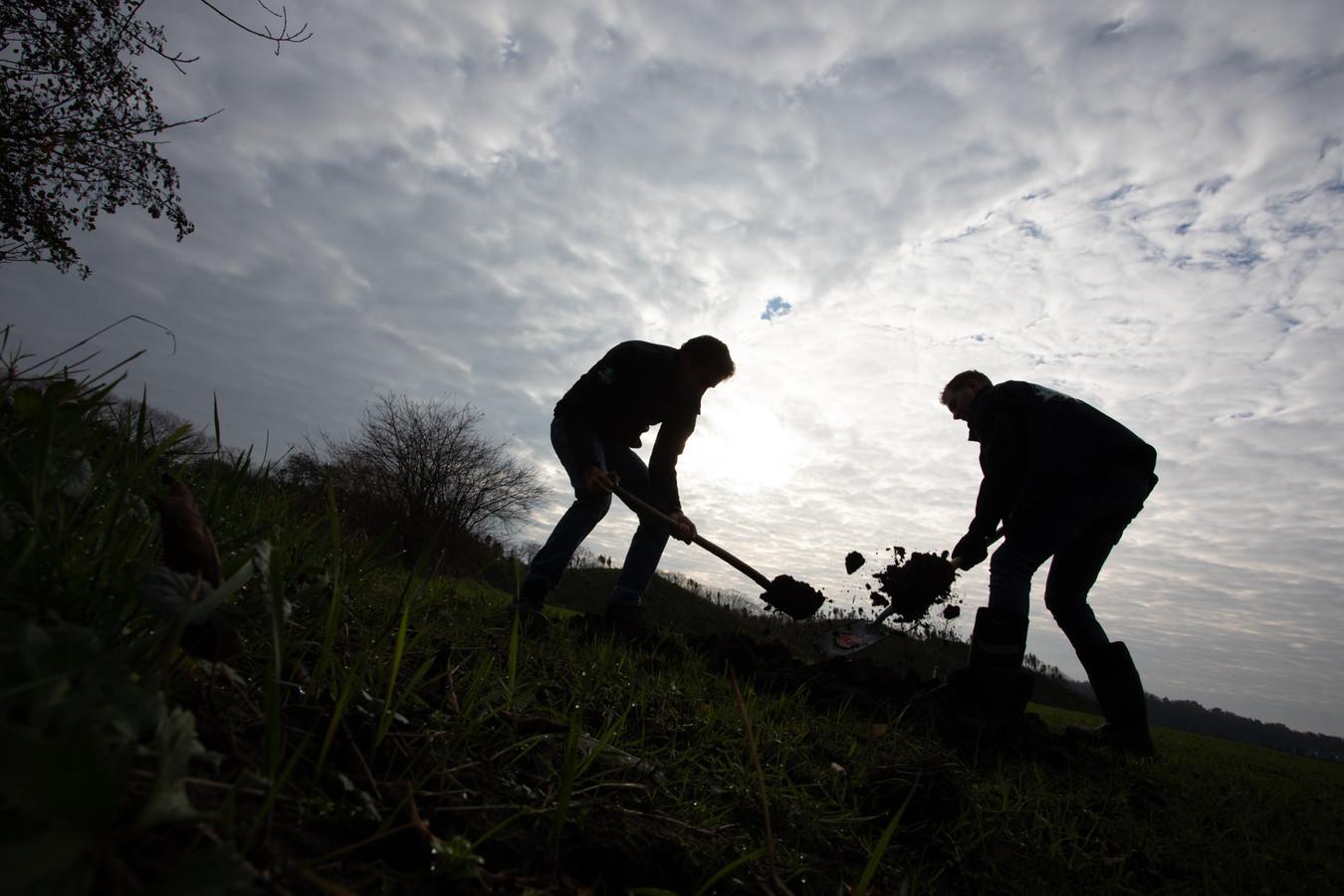 Vrijwilligers van Intents aan het werk om het retentiebekken achter Sportpark Den Donk in het groen te zetten