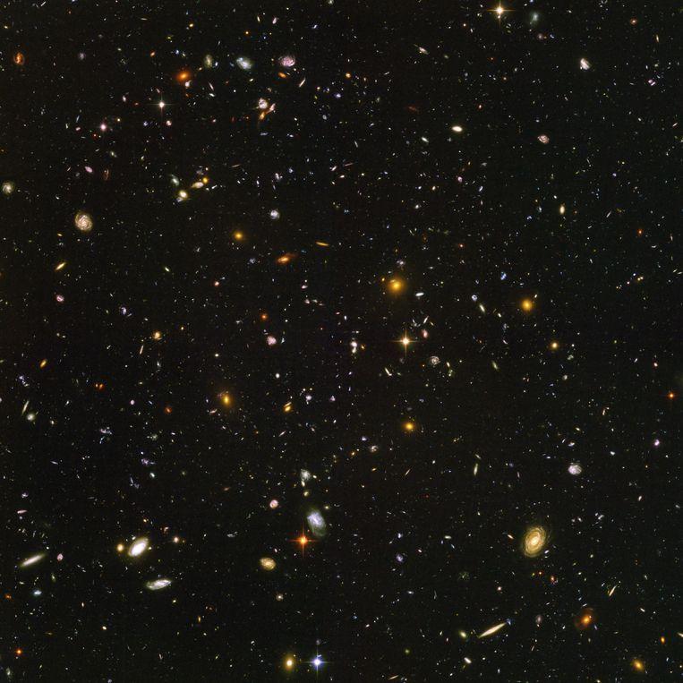 Op deze foto uit 2004, een opvolger van de oorspronkelijke Hubble Deep Field-foto, duiken zo'n 10.000 sterrenstelsels op. De vaagste rode vlekjes zijn stelsels zoals ze 800 miljoen jaar na de geboorte van het heelal ontstonden. De grotere, heldere stelsels zijn veel jonger: die ontstonden toen het heelal al 13 miljard jaar oud was. Beeld NASA, ESA
