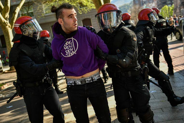 Een van de demonstranten wordt weggevoerd.