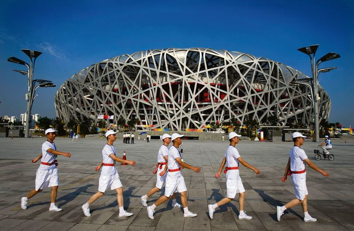 Vrijwilligers op het plein voor het Olympisch stadion in Peking in 2008. China zette in totaal 100.000 vrijwilligers in tijdens de Spelen.