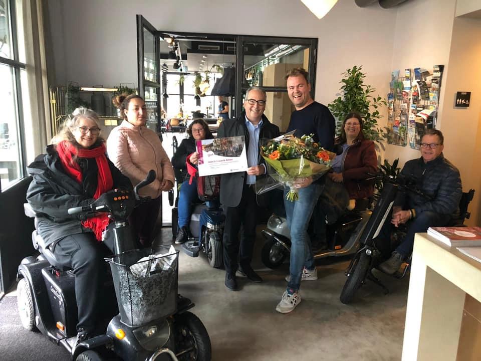 Ron Diephout van Katoen krijgt een oorkonde en een bloemetje van wethouder André van der Reest.