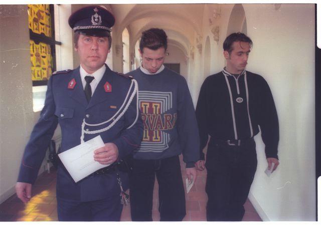 Een rijkswachter begeleidt Rosies zonen Tom en Pieter Kerckaert in het Brugse assisenhof als getuigen in het proces tegen hun moeder.
