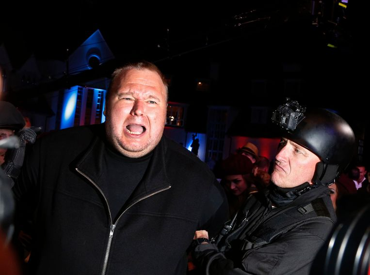 An actor in police costume mock-arrests Megaupload founder Kim Dotcom (L) as he launches his new file sharing site