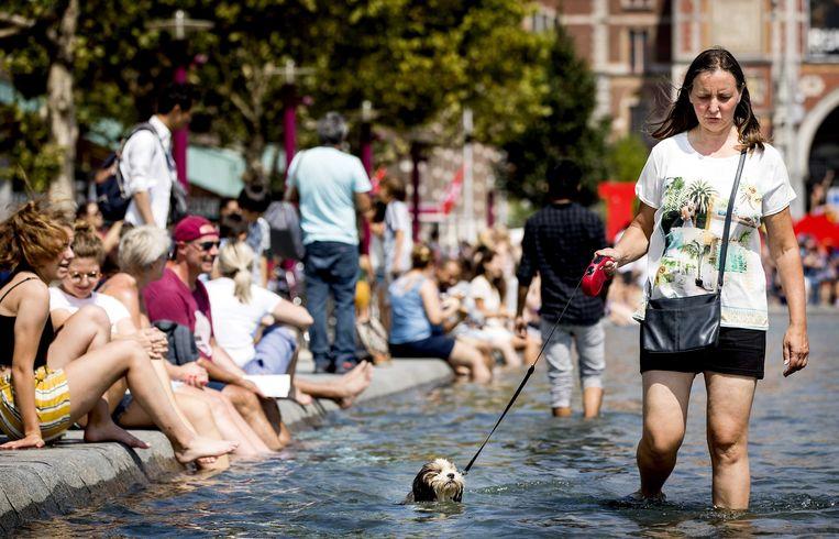 Toeristen zoeken verkoeling op het Museumplein in Amsterdam. De meeste toeristen in de hoofdstad komen uit Duitsland. Beeld EPA/Koen van Weel