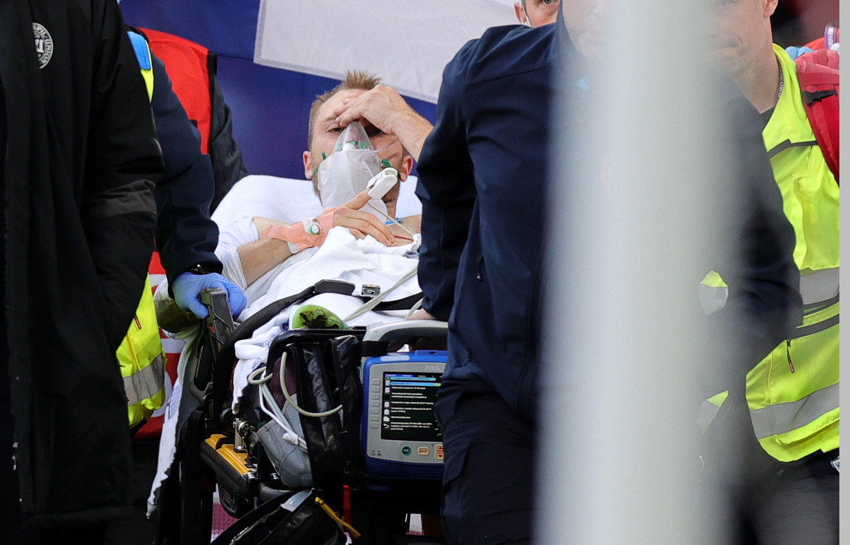 De Deense international Christian Eriksen wordt op een brancard van het veld gereden. Beeld EPA