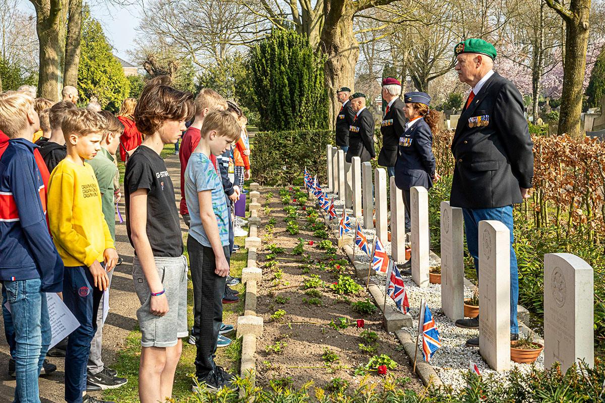 Bij de graven van de geallieerden leggen leerlingen van de Nutsschool een roos.