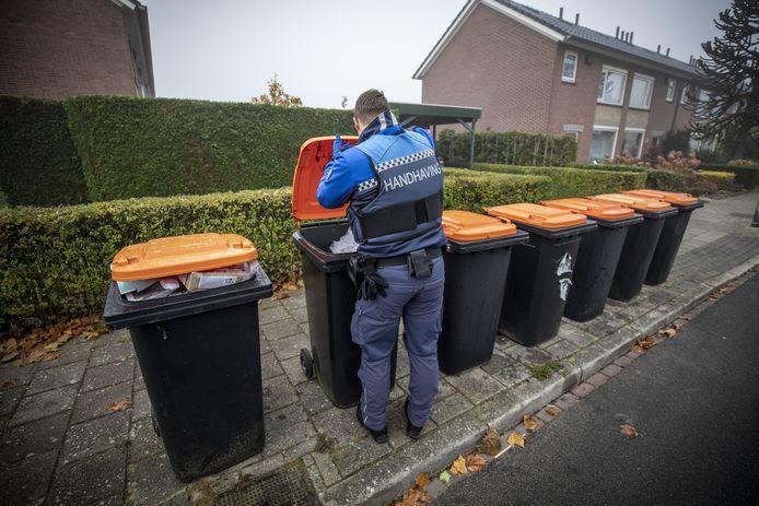 Een handhaver van de gemeente Oldenzaal controleert of er afval in de container zit dat er niet in hoort.