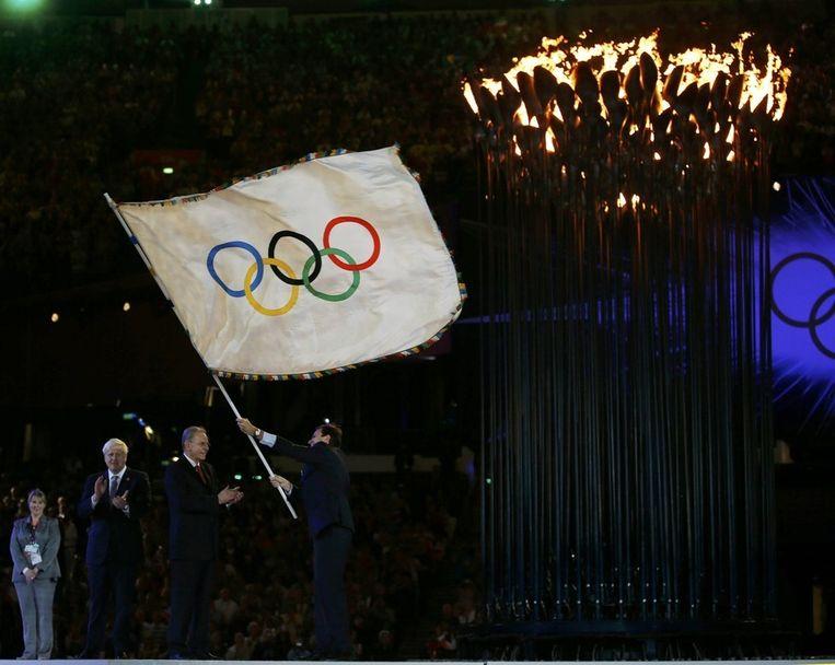 De Londense burgemeester Boris Johnson (links) heeft de vlag overhandigd aan zijn collega Eduardo Paes van Rio de Janeiro, waar de Spelen in 2016 worden gehouden. In het midden IOC-voorzitter Rogge. Beeld reuters