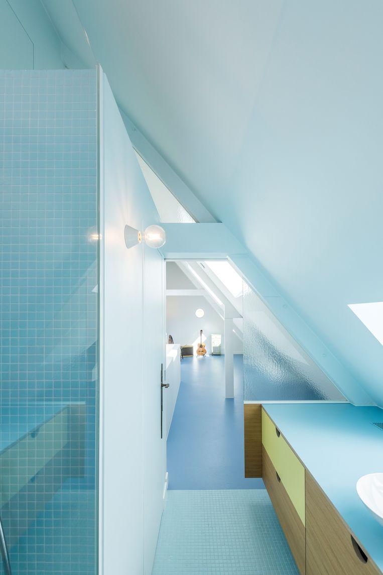De zolder is een open ruimte. Door te spelen met verschillende tinten blauw wordt de badkamer toch gescheiden van de slaapkamer.   Beeld Luc Roymans