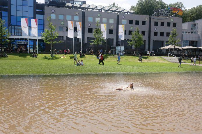 Een zwemmer kan het toch niet laten en zwemt in het ondergelopen deel van de Waalkade.