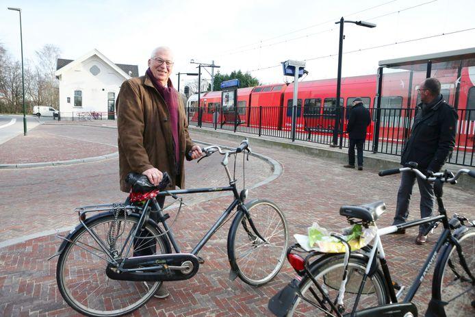 Wethouder Jan de Groot arriveert met zijn fiets bij het station waar net een trein binnenkomt. Achter hem ligt de keerlus.