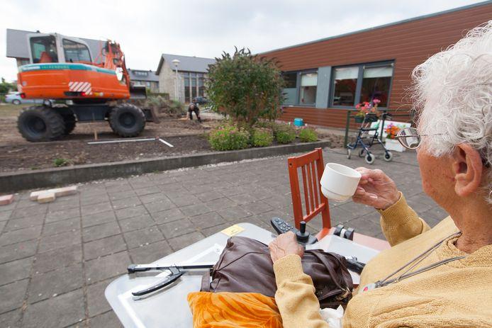 Een bewoonster van ouderencomplex Zuidervaart in Alphen volgt de aanleg van een tuin. Op de plek van Zuidervaart komen dit jaar 43 koopwoningen.