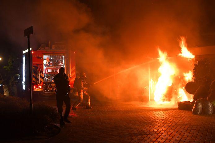 Een felle autobrand onder een carport in Putten