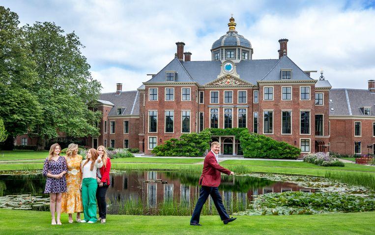 Koning Willem-Alexander geeft persfotografen de ruimte voor een portret van koningin Máxima en de drie prinsessen in de paleistuin van Huis ten Bosch.   Beeld Raymond Rutting / de Volkskrant