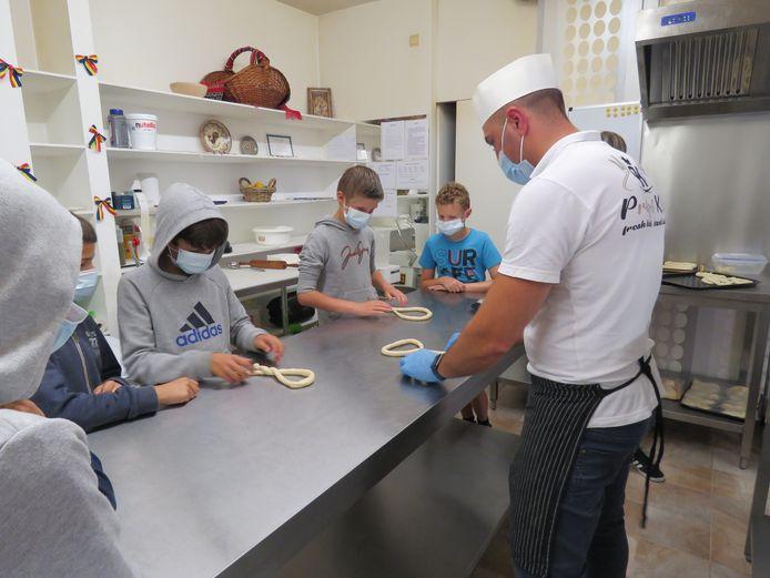 De kinderen leren hoe je een pretzel vouwt.