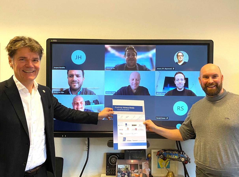 Burgemeester Paul Depla (links) en wethouder Boaz Adank van Breda bij de online presentatie van Roadmap Horeca. Via schermen kijken vertegenwoordigers van de betrokken partners toe.