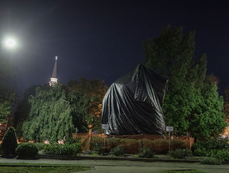 Ondertussen, in Charlottesville: het controversiële standbeeld van de 'zuidelijke' generaal Robert Edward Lee wordt onder een dekzeil verstopt tot de wet toelaat dat het ook letterlijk van zijn voetstuk gehaald mag worden. Blanke nationalisten zijn daar hevig tegen.  Beeld © Espen Rasmussen/Verdens Gang/Panos Pictures