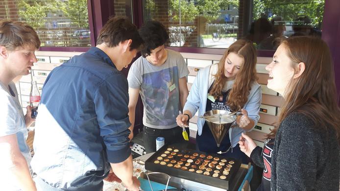Jongeren bakken poffertjes voor ouderen