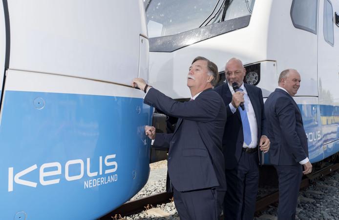 Cees Anker (voorgrond) onthult zijn naam op de trein. Op de achtergrond staat Bert Boerman klaar om hetzelfde te doen. In het midden operationeel directeur Emile Broersma van Keolis Nederland.