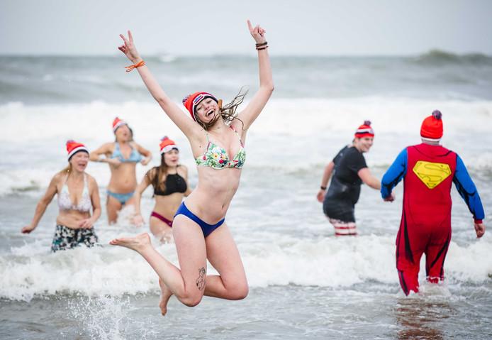 Deelnemers aan de traditionele Unox Nieuwjaarsduik rennen de Noordzee in voor een verfrissende duik.