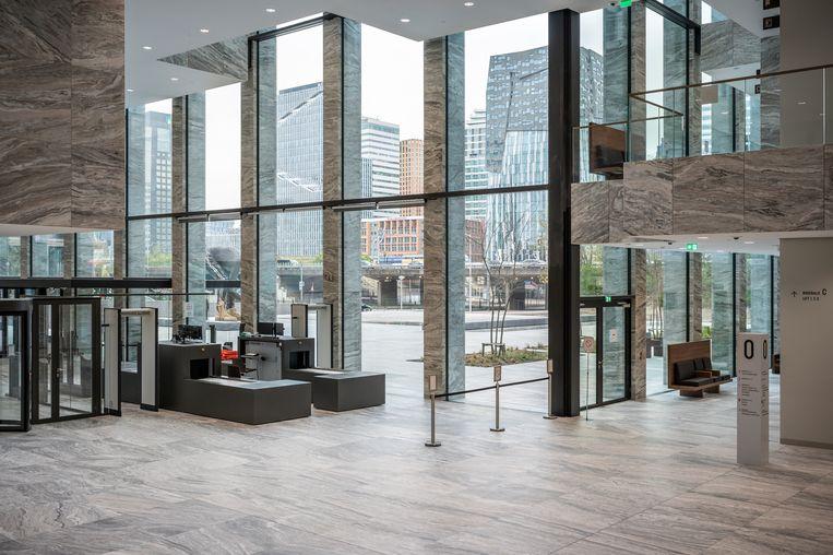 De foyer met blik naar buiten. De natuurstenen vloer loopt door op het plein. Hier wordt de gewenste connectie met de stad zichtbaar. Beeld Tom Philip Janssen
