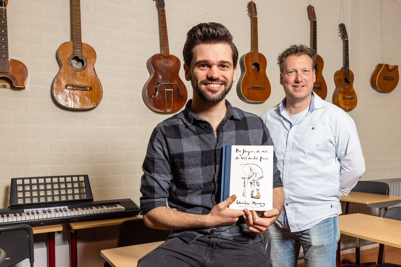 Docent René van Gerven (rechts) van het Rodenborch College met oud-leerling Jurrian Marx die muziek componeert bij het boek 'De jongen, de mol, de vos en het paard'.