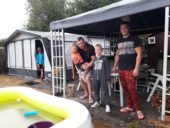 Camping De Bosfazant in Moergestel: Ruud Zirkzee met zijn familie schuilt voor de regendruppels.