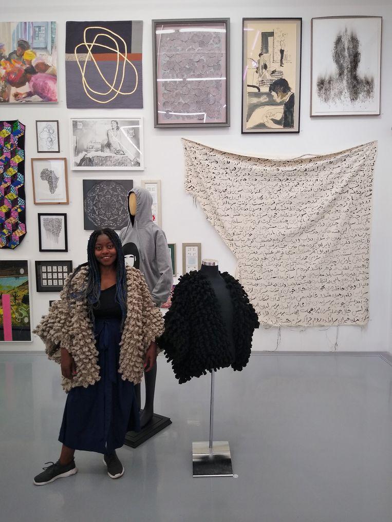 De 29-jarige textielkunstenares Diana Zitha naast haar zwarte mantelontwerp met de titel 'Gunguwo' (De kraai) op de tentoonstelling 'Home is where the art is'.  Beeld Niels Posthumus