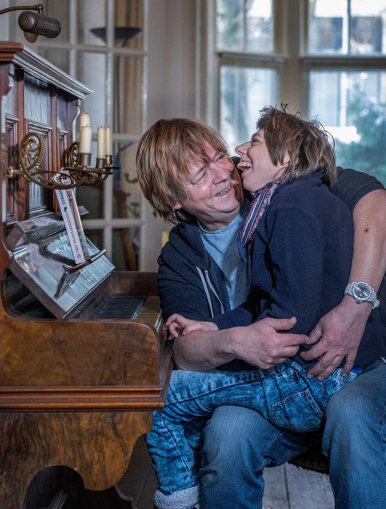 Guido Bindels en zijn dochter Brigitte, thuis in Dordrecht. 'Brigitte kan niet goed zitten, ze heeft scoliose, dus hangen we meestal op de bank, tegen elkaar aan.' Beeld Patrick Post