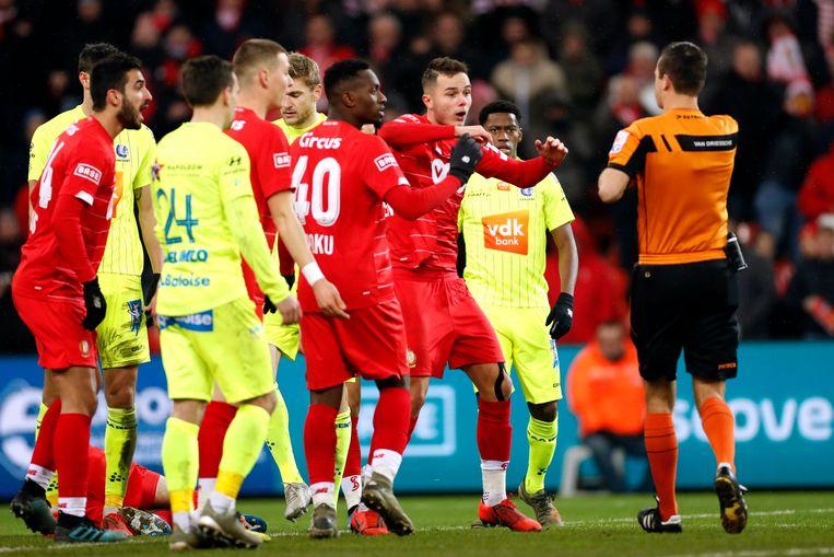 Ref Van Driessche maant de spelers tot kalmte aan. Beeld Photo News