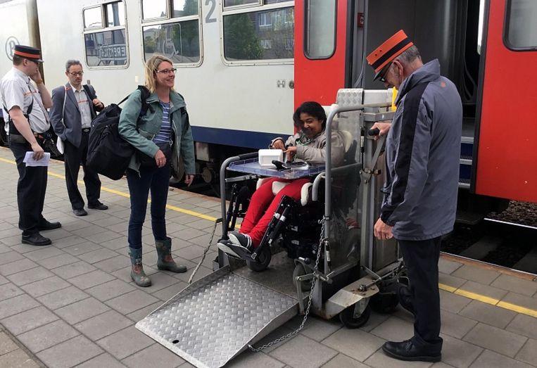 Inne Vennekens helpt een rolstoelpatiënt uitstappen.