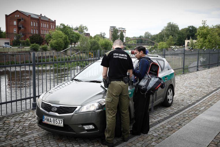 Een Poolse agent controleert, zestig minuten lang, de papieren van een migrant. Beeld Daniel Rosenthal / de Volkskrant