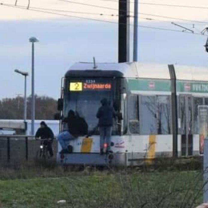 Twee jongeren die meesurfen met de tram