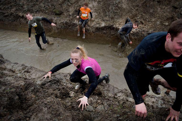 Deelnemers tijdens de jaarlijkse Mud Masters Obstacle Run op het voormalig Floriadeterrein in de Haarlemmermeer. Beeld ANP