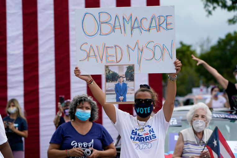 Een Democratische kiezer maakt duidelijk wat ze van Obamacare vindt, op een meeting van presidentskandidaat Biden, waar Obama speechte. Beeld AP