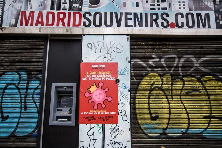 """16-03-20 Madrid-Spain  Een gesloten souvenirwinkel in de Spaanse hoofdstad. De affiche waarschuwt voor Covid-19: """"Het enige souvenir dat we u niet willen meegeven uit Madrid."""" Beeld Photo News"""