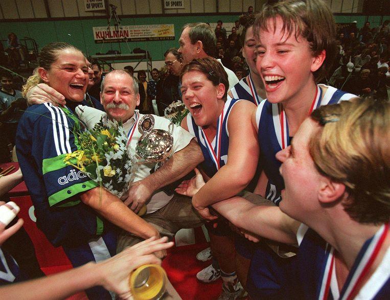 Meindert van Veen, eind jaren '90 coach van de basketbal-dames uit Den Helder, wordt door zijn meiden in de feestvreugde betrokken. Beeld ANP