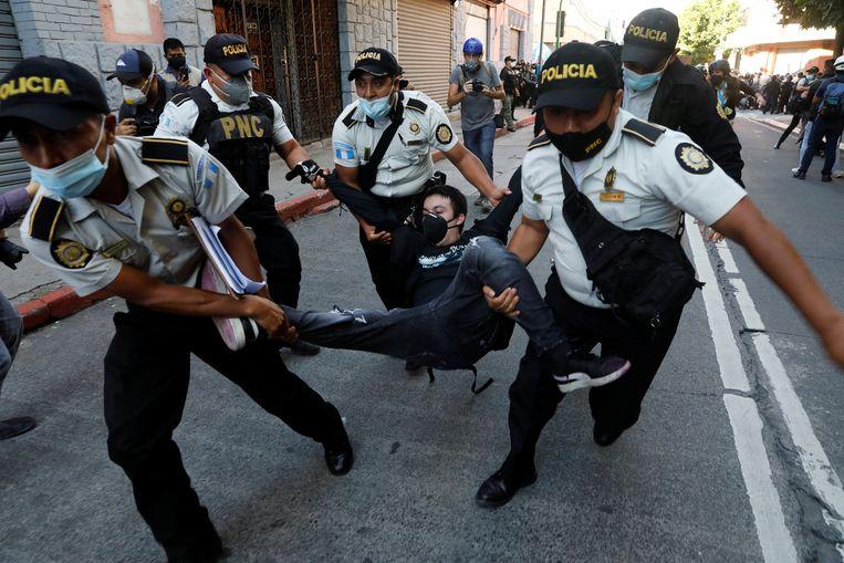 Politie-agenten voeren een betoger mee. Beeld REUTERS
