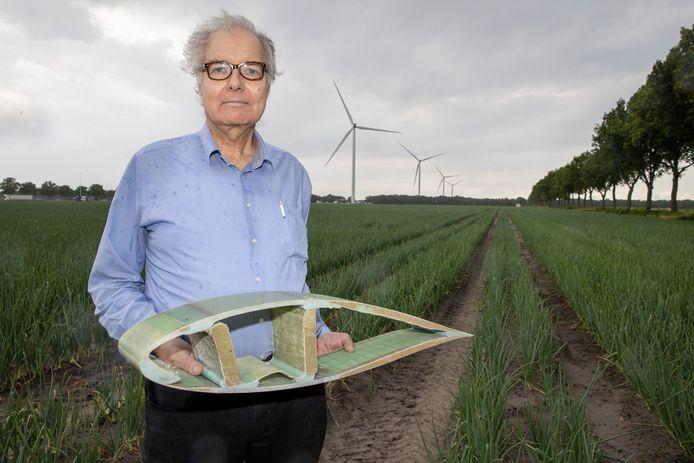 Henk Daalder, met in zijn hand een deel van een wiek van een molen. Op de achtergrond de Oirschotse windmolens.