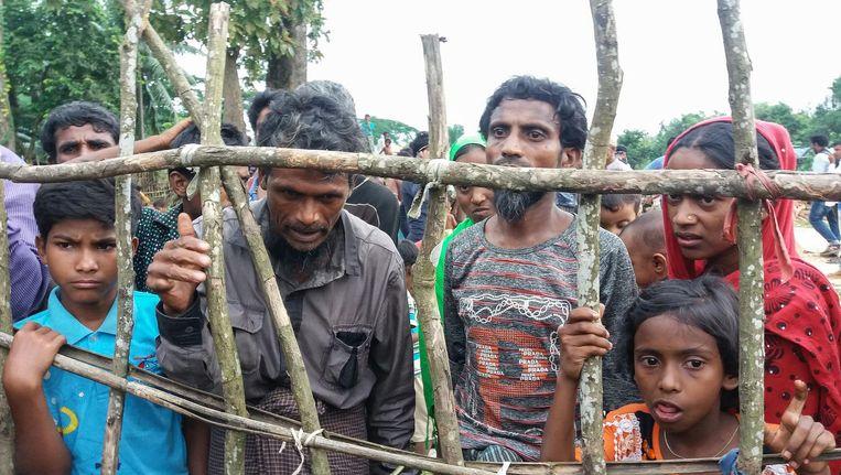 Rohingya-vluchtelingen bij het hek van een kamp in Bangladesh. Beeld afp