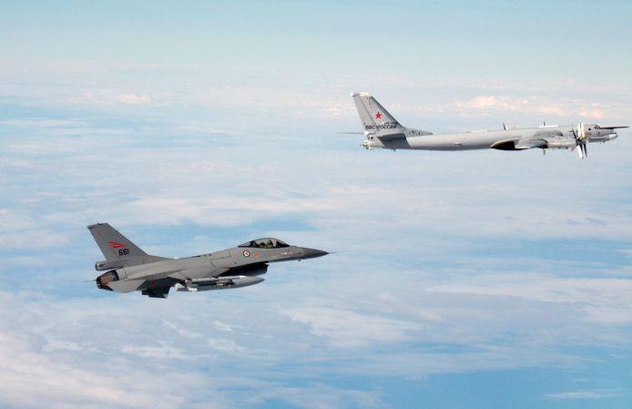 Archiefbeeld van Noorse F-16 die blak bij een Russische Tu-95 bommenwerper  vliegt